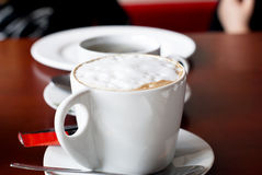 White china cup of coffee with a frothed milk top Royalty Free Stock Photography