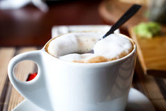 White china cup of coffee with a frothed milk top Royalty Free Stock Images