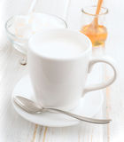 White china mug full of milk, sugar and honey Royalty Free Stock Photography
