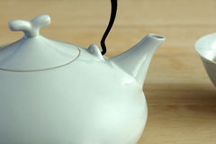 White china pot and cup. White tea pot and cup with spoon on the table Stock Photos