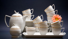 White china tea-set with flower on blue Royalty Free Stock Images