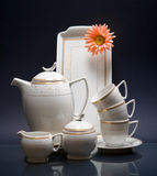 White china tea-set with red flower on blue Stock Image