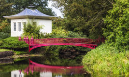 White Chinese house and red iron bridge. Shugborough, Staffordshire, England July 13th 2013 Shugborough hall Chinese house built in 1747 and new red Iron foot Stock Photography