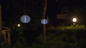 House yard with Chinese lanterns at night. White Chinese lanterns hanging in dark house garden at night stock footage