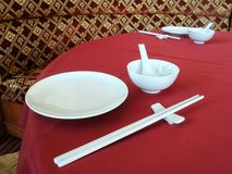 White Chinese tableware on red table cloth. White chopsticks and rice bowl on  Chinese dining table Stock Photo