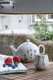 White Chinese teapot with cup of tea on the woven mat and white towel with some berries. On the window royalty free stock images