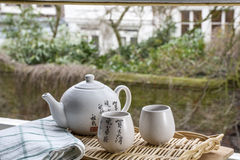 White Chinese teapot with cups on the woven mat on window Stock Image