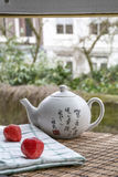 White Chinese teapot with cups on the woven mat on window Stock Photography