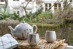 White Chinese teapot with cups on the woven mat on the window Stock Images