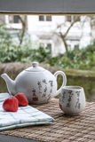 White Chinese teapot on the woven mat on the window Royalty Free Stock Image