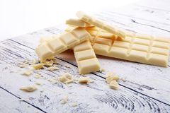 White chocolate bars and white choco pieces on wood. White chocolate bars and white choco pieces on wood Royalty Free Stock Photos