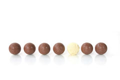 White chocolate among brown ones. To be different - a white chocolate among a row of brown ones Royalty Free Stock Photography