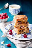 White chocolate cake, blondie, brownie with cranberry and coconut. On a white and blue wooden background Stock Photo
