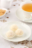 White chocolate candies with tea. Decadent white chocolate and coconut candies with refreshing herbal tea in vertical format Stock Photography