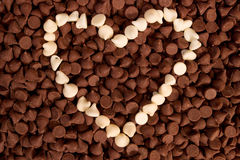 White Chocolate Chip Heart. White chocolate chips arranged into a heart shape on a bed of milk chocolate chips royalty free stock image