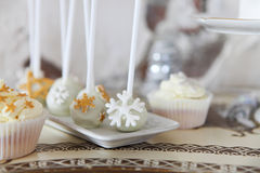 White chocolate Christmas cake pops with snowflakes and cupcakes Royalty Free Stock Photo