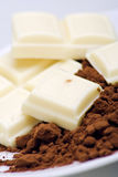 White chocolate and cocoa. Segments of white chocolate with cocoa powder Stock Photography