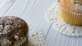 White and chocolate cupcakes on white wooden table. Focus from one to another.  stock video footage