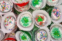 White chocolate dipped cookies decorated and packaged for Christmas, with sugar sprinkles and jimmies. In various colors royalty free stock image