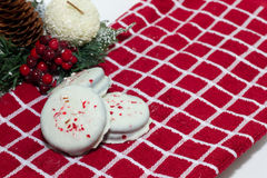 White Chocolate Dipped cookies sprinkled with crushed peppermint. Homemade white chocolate chip dipped cookies on a checkered background stock image