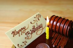 White Chocolate Greeting Card with a Lighting Yellow Candle on Chocolate Mousse Birthday Cake. On the Wooden Table stock image