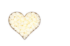 White chocolate morsels fill a silver heart. White background royalty free stock image
