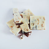 White chocolate with nuts, raisins on a background Stock Photos