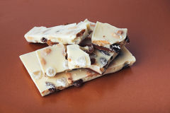 White chocolate with nuts, raisins on a brown background Royalty Free Stock Photos