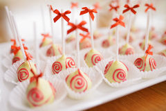 White chocolate pops. White chocolate candies decorated with red ribbons Stock Images
