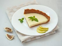 White chocolate tart decorated with lime slices, fresh mint and dried lime. Selective focus. royalty free stock image