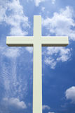 White Christian cross in front of a cloudy sky Royalty Free Stock Photography