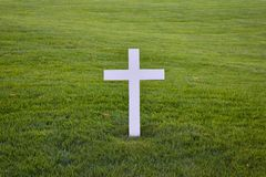 White Christian Cross surrounded by green grass royalty free stock photo
