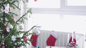 White Christmas à moda interior com a árvore de abeto decorada, peúgas, velas, festão, patins do inverno pela janela lento video estoque