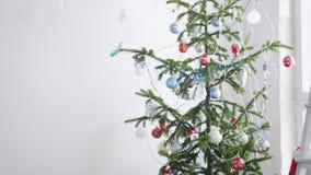 White Christmas à moda interior com a árvore de abeto decorada pela janela Movimento lento 3840x2160, 4K vídeos de arquivo