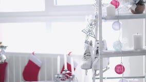 White Christmas à moda interior com escada portátil decorada, peúgas, velas, festão, patins do inverno pela janela lento filme