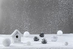 White Christmas background with a blowing snow over on grey background, bauble, house, pine cone stock image