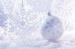 White Christmas ball on white background with snowflakes and bokeh. Christmas background .