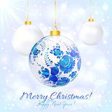White christmas ball with blue floral ornament. And golden ribbon Stock Photography
