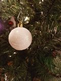White Christmas ball decorations. Hanging from a Christmas tree with lights Royalty Free Stock Image