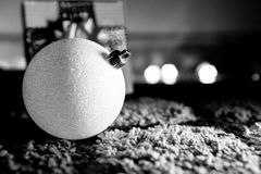 White Christmas Ball with Gift in Background Low Key. Sparkly White Christmas Ball with Gift in Background Black And White Low Key Stock Image