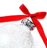 White Christmas Ball with Red Ribbon on a snow on white backgrou Royalty Free Stock Photography