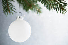 White christmas ball on the xmas tree on glitter bokeh background. Merry christmas card. Stock Images