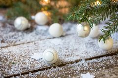 White Christmas balls, evergreens and snow on wooden underground. Selective focus royalty free stock photo
