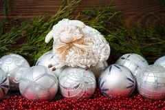 White christmas balls and  nice sheep with wooden. White christmas balls and cute sheep on  wooden background Royalty Free Stock Image