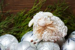 White christmas balls with nice sheep wooden. White christmas balls and cute sheep on  wooden background Royalty Free Stock Photography