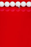 White christmas balls in a row on the red background vertical Royalty Free Stock Photo