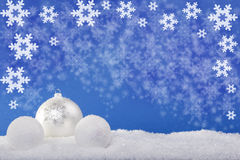 White Christmas balls in the snow. With a blue background royalty free stock photography