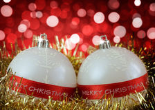 White Christmas baubles with Merry Christmas sign. On background of defocused  lights Stock Image