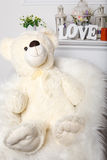 White christmas bear. Sitting in artificial snow royalty free stock image