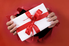 White Christmas or birthday surprise gift with ribbon being delivered through a red torn paper background Royalty Free Stock Photos